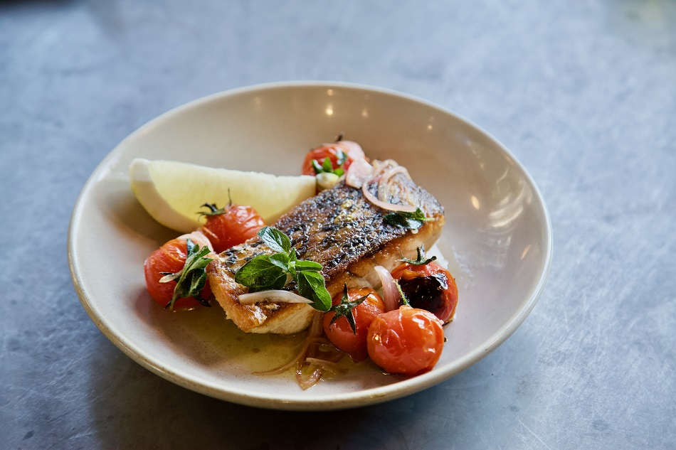 Image of a plated meal of cooked barramundi with cherry tomatoes