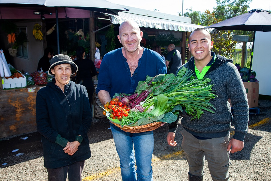 Matt Moran holding a basket of Mrs Sun's veggies take from Western Sydney Parklands Urban Farms