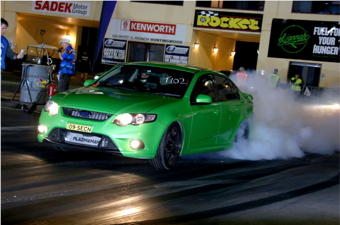 Image of green car burning rubber at Sydney Dragway