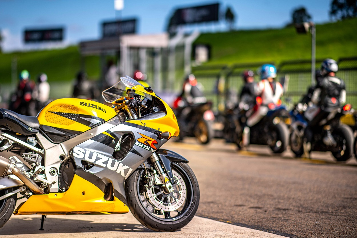 yellow motorbike with racers in the background